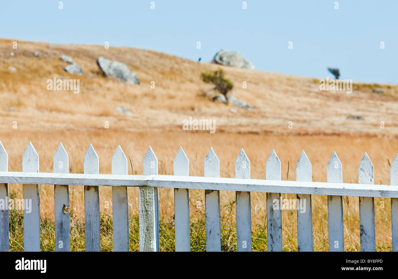 A white picket fence and landscape beyond at the American Camp National Historical Park, San Juan Island, Washington, - Stock Image