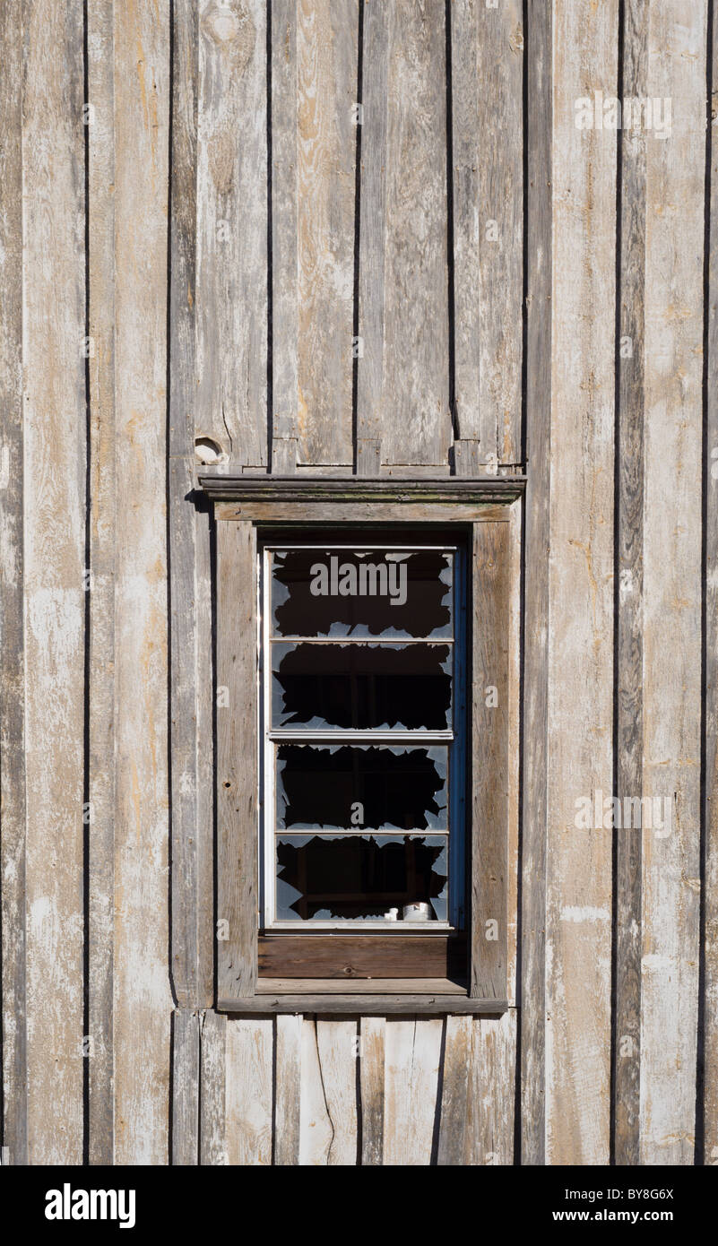 An old wooden building with a broken window, on the Mescalero American Indian reservation, New Mexico. - Stock Image