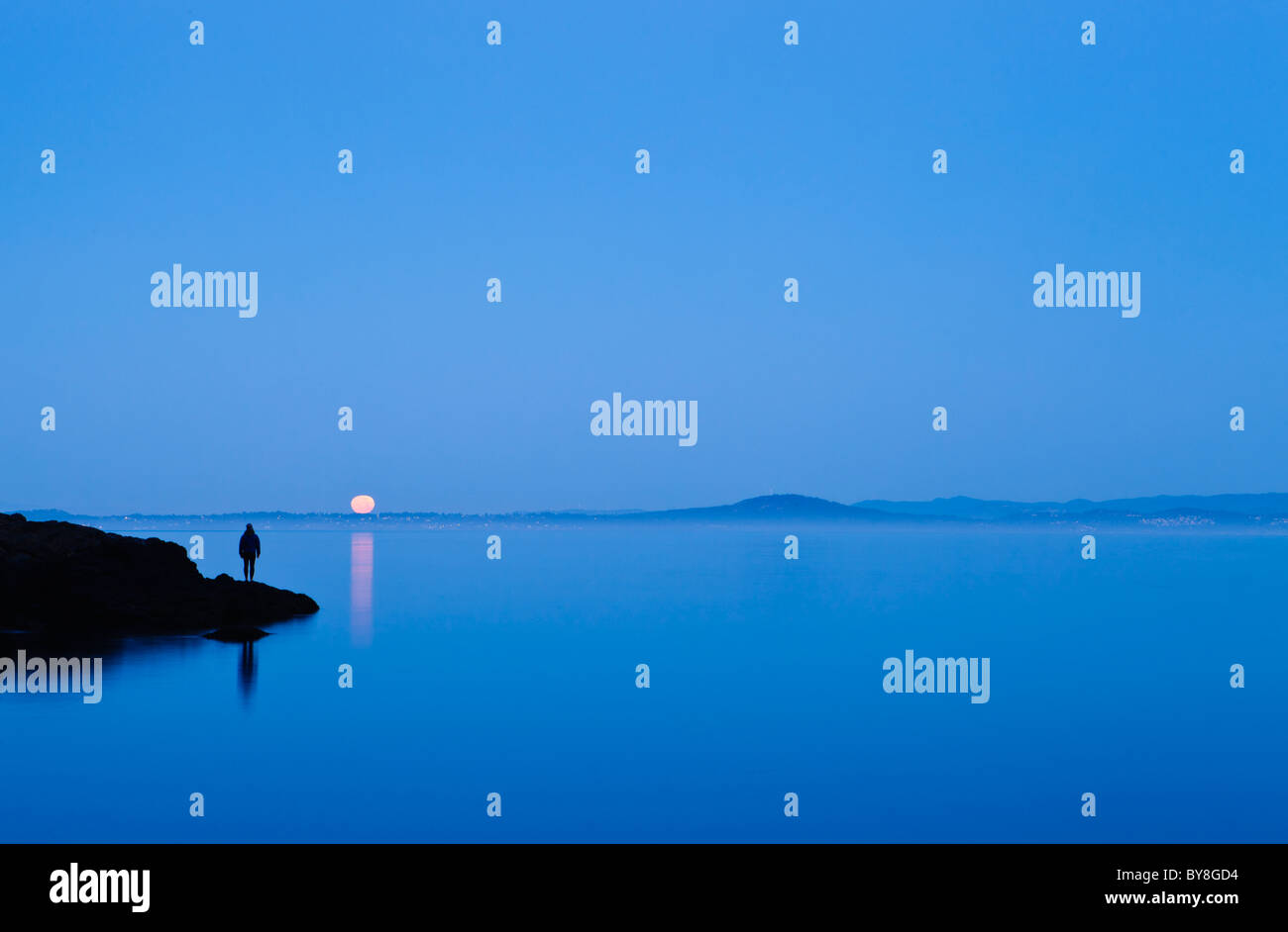 A woman stands on a shoreline watching the setting full moon over Haro Strait and Vancouver Island, San Juan Island, - Stock Image