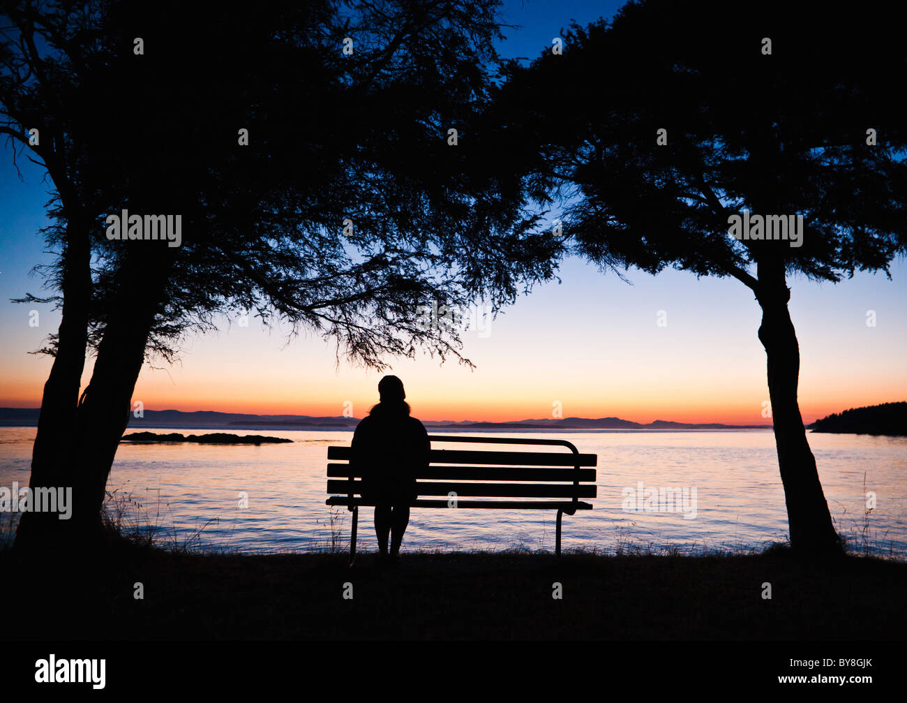 A woman sitting alone on a park bench overlooking a body of water at sunset. - Stock Image