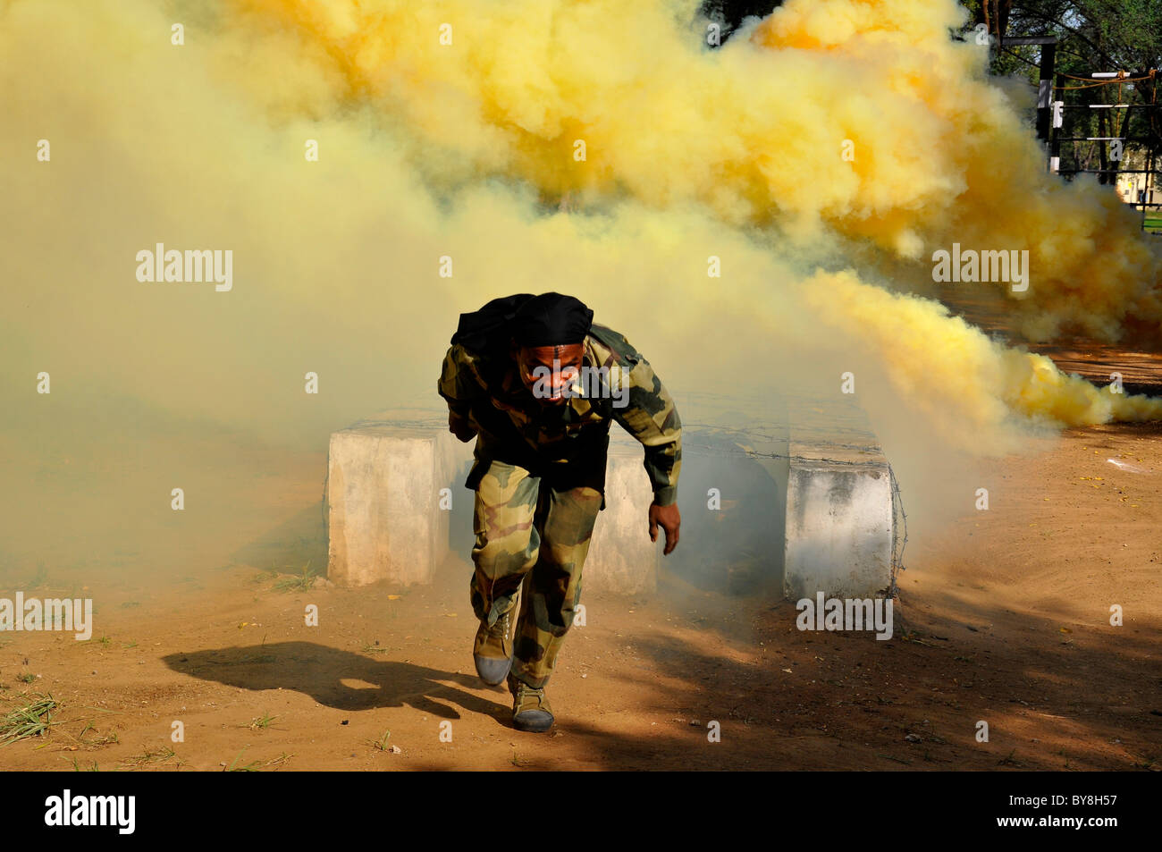 An indian anti-terrorist commando coming out of obstacle in a smoky atmosphere - Stock Image