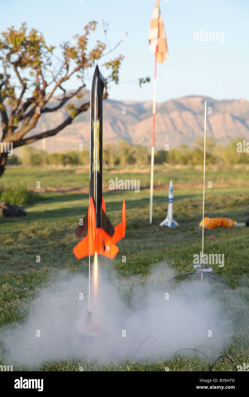 colorful model rocket launching off grass - Stock Image