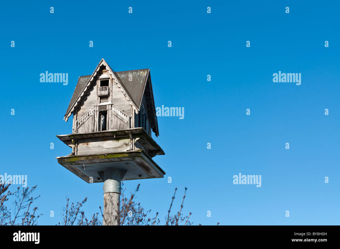 A birdhouse sits atop a pole with a deep blue sky in the background. - Stock Image