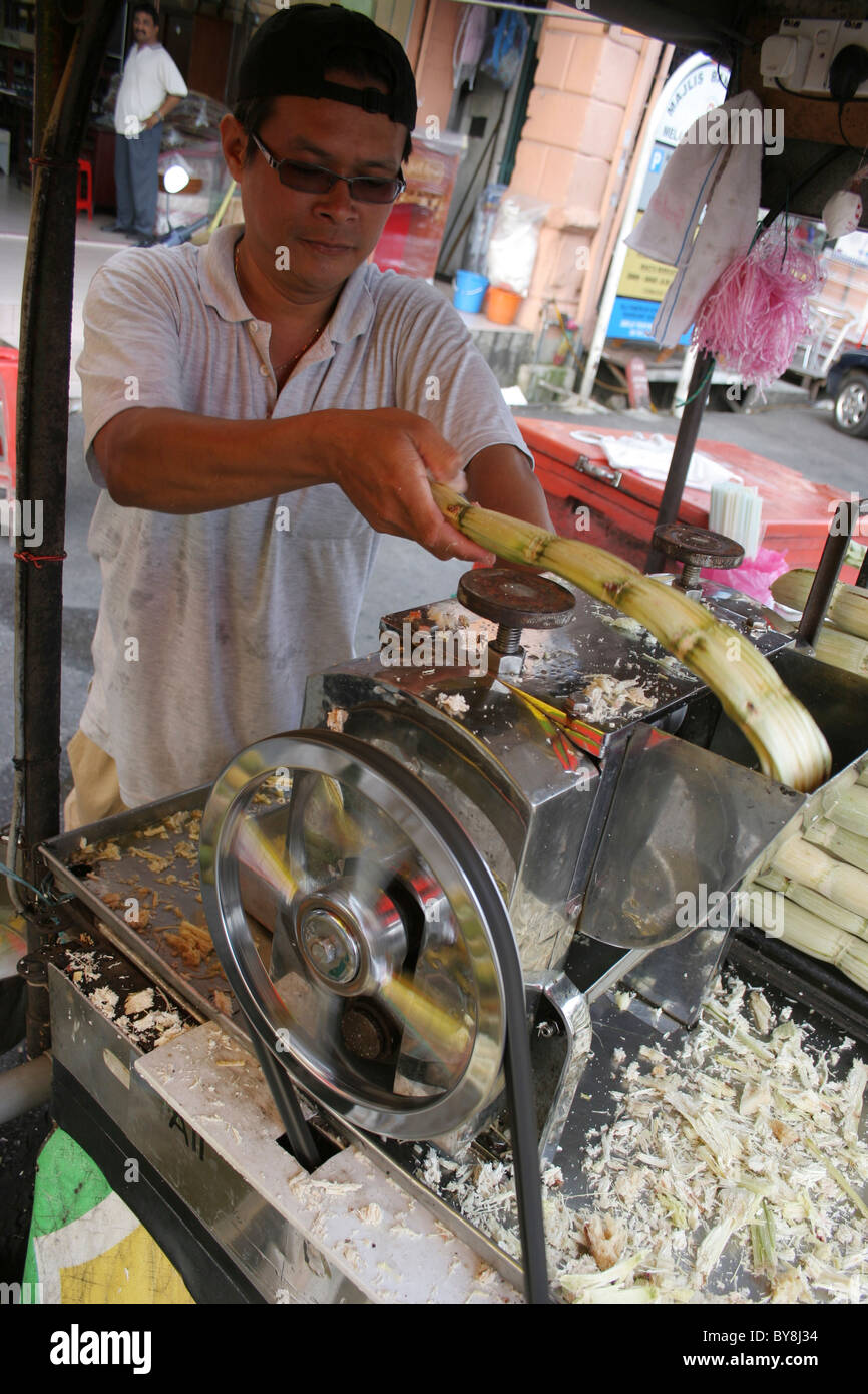 Crushing suger cane in a mangle to extract the juices and make a drink - Stock Image