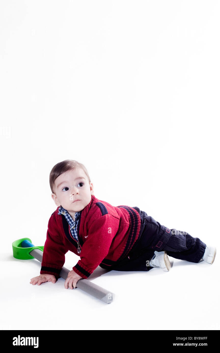 One Year Old Boy Crawling and taking his  sword - Stock Image