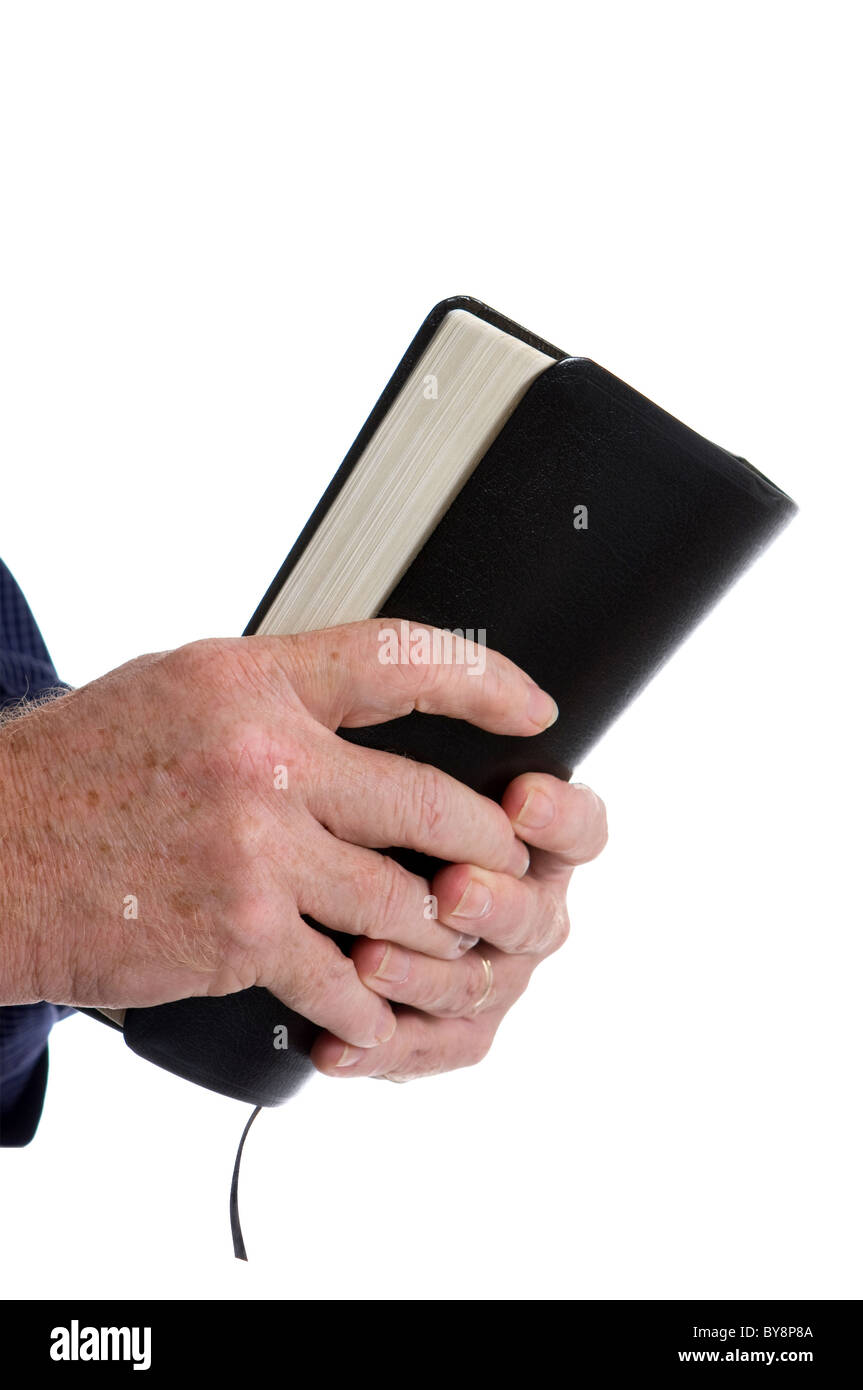 Missionary man's hands clutch Holy Bible. Isolated on white. Room for copy at top. - Stock Image