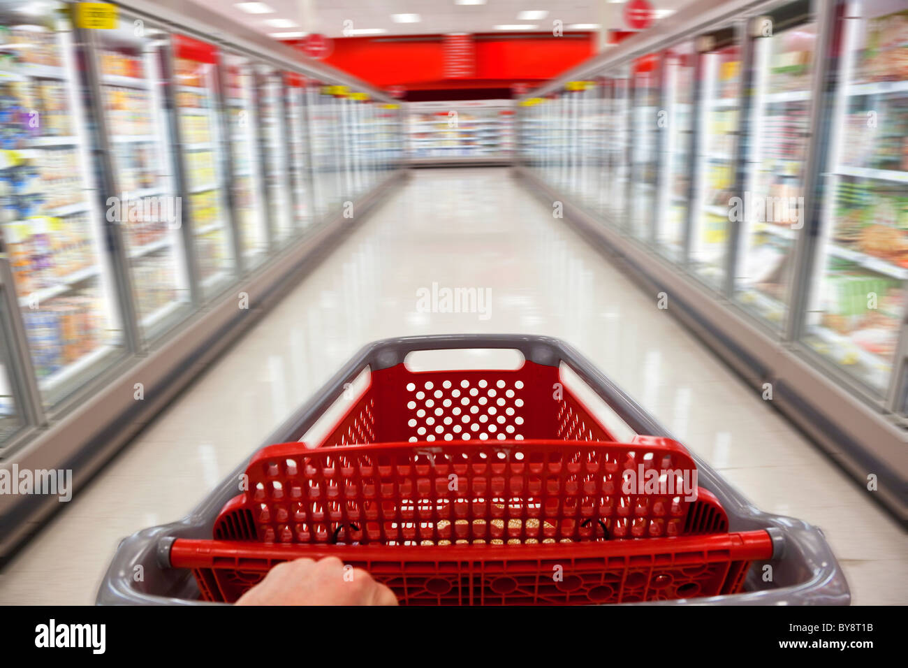 A fast food concept motion blur shot of a shopping trolley being pushed down the aisle of a supermarket - Stock Image