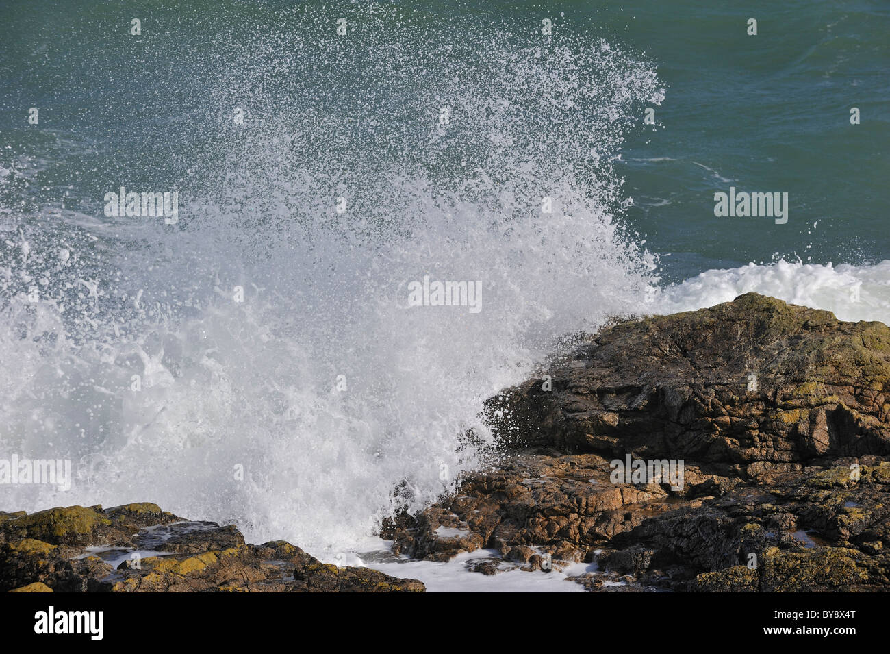 Waves crashing onto rocks along the Normandy coast, France - Stock Image