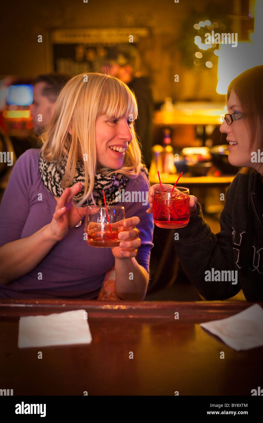 girls with red drinks at bar - Stock Image