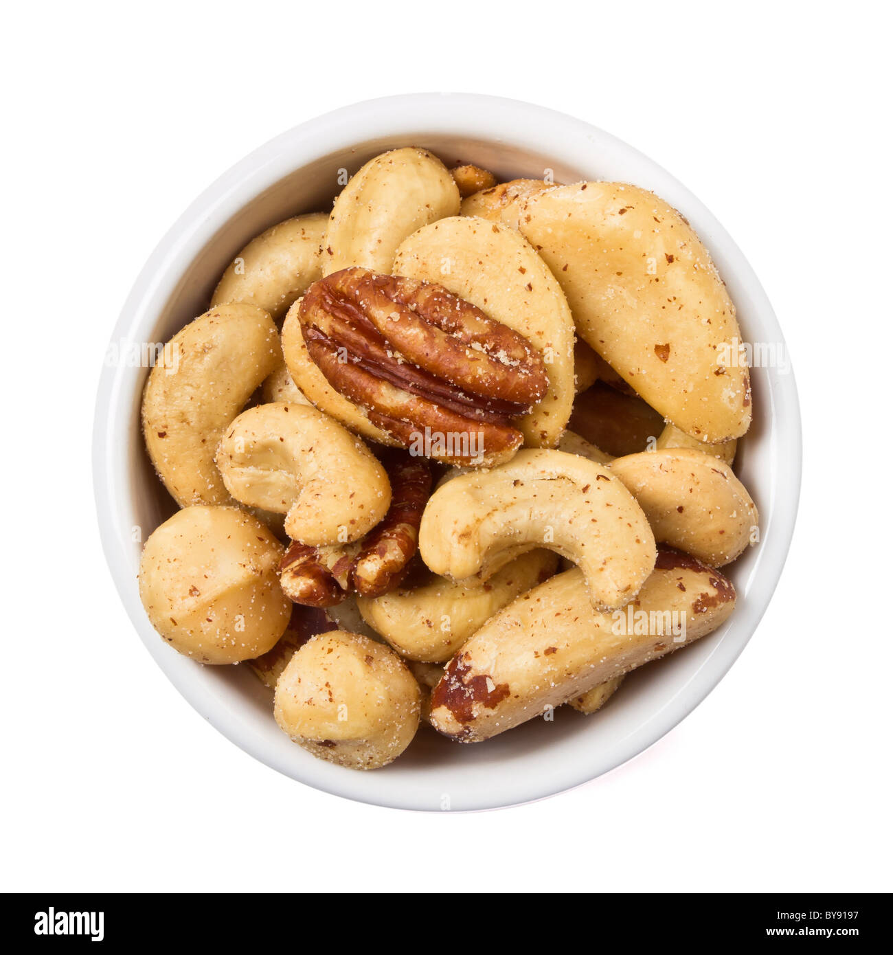 Mixed Salted Nuts in bowl overhead view isolated on white. - Stock Image