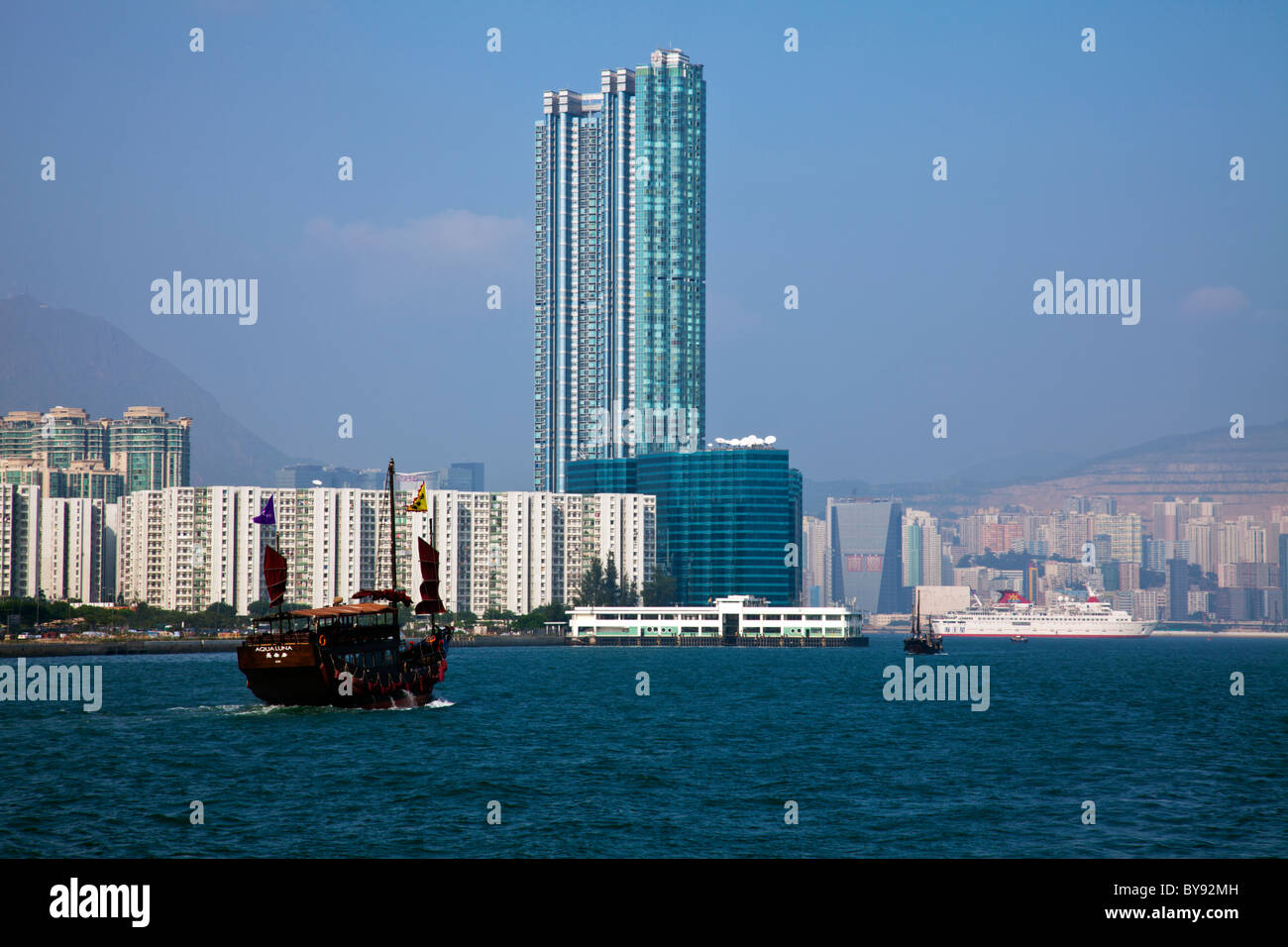 The Kowloon skyline in the day showing the iconic Chinese Junk sail boat on Victoria Harbour, Hong Kong - Stock Image