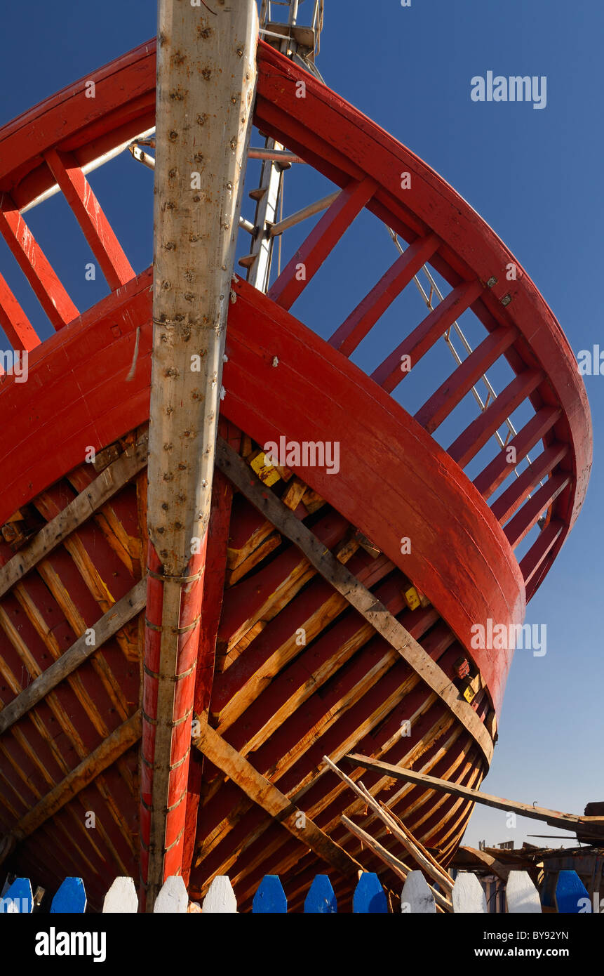 Red wooden boat under construction at the Essaouira Port in Morocco - Stock Image