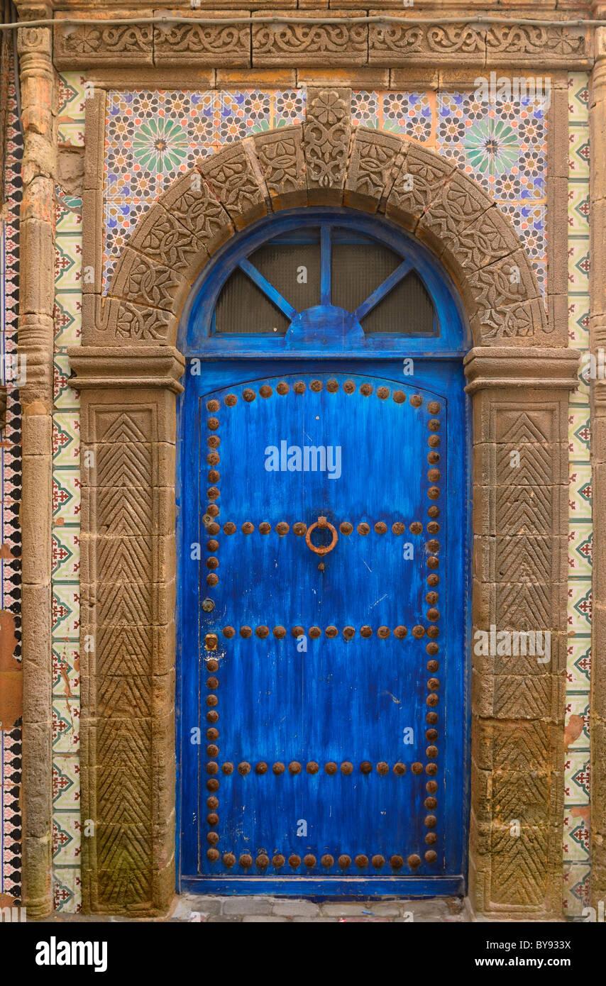 Blue door in Essaouira Medina with ornate stonework and Zellige tilework Morocco - Stock Image