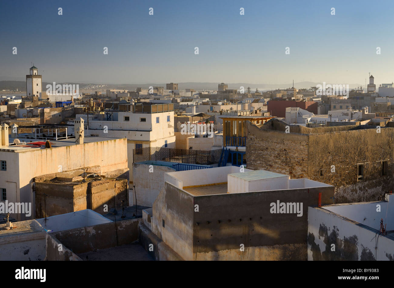 Overview of rooftops in Essaouira Morocco and Atlantic ocean beach and wind turbines in distance - Stock Image