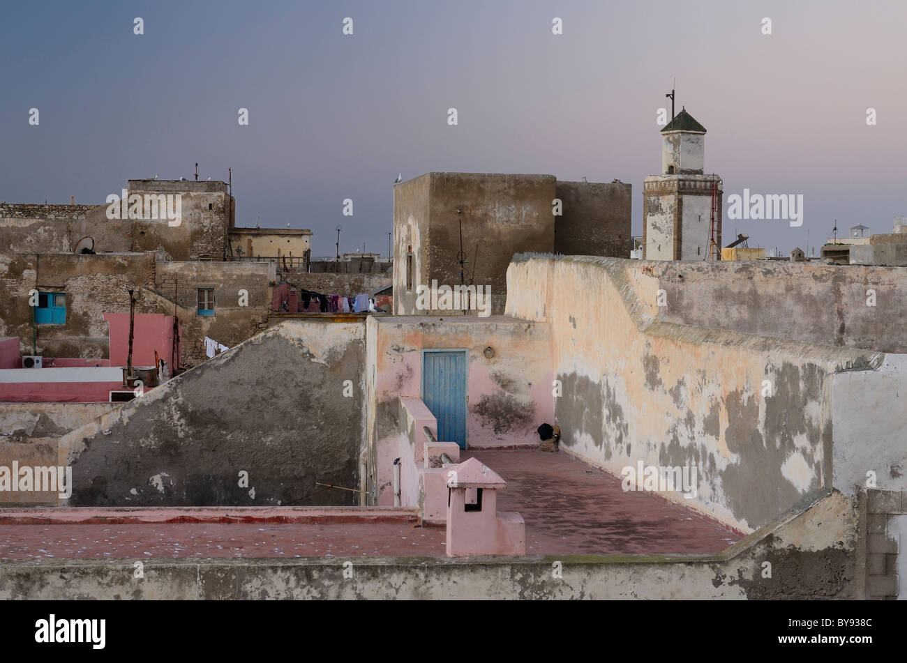Soft pastel pink and blue colors at dawn over rooftops of Essaouira Morocco - Stock Image