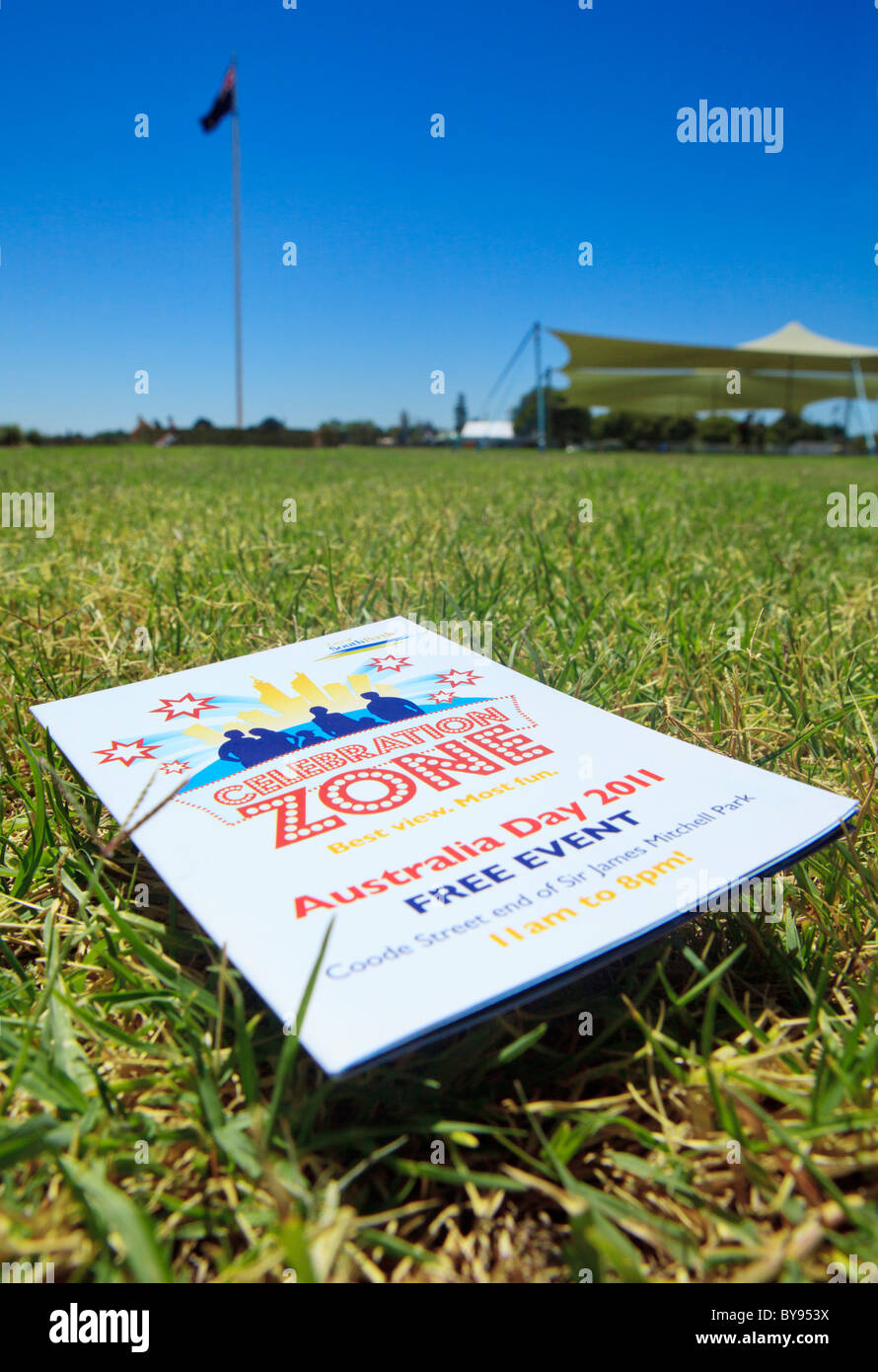 Australia Day celebrations booklet with the Australian flag in the distance - Stock Image