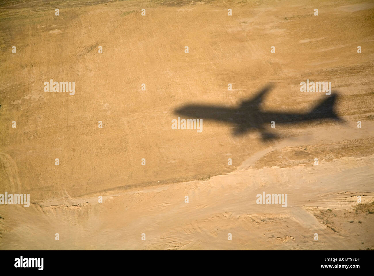 Shadow of a flying airplane taking off - Stock Image