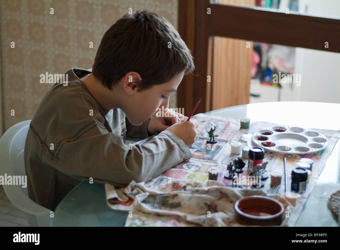 France Ten Years Old Boy Painting His Figurine In The Kitchen - Stock Image