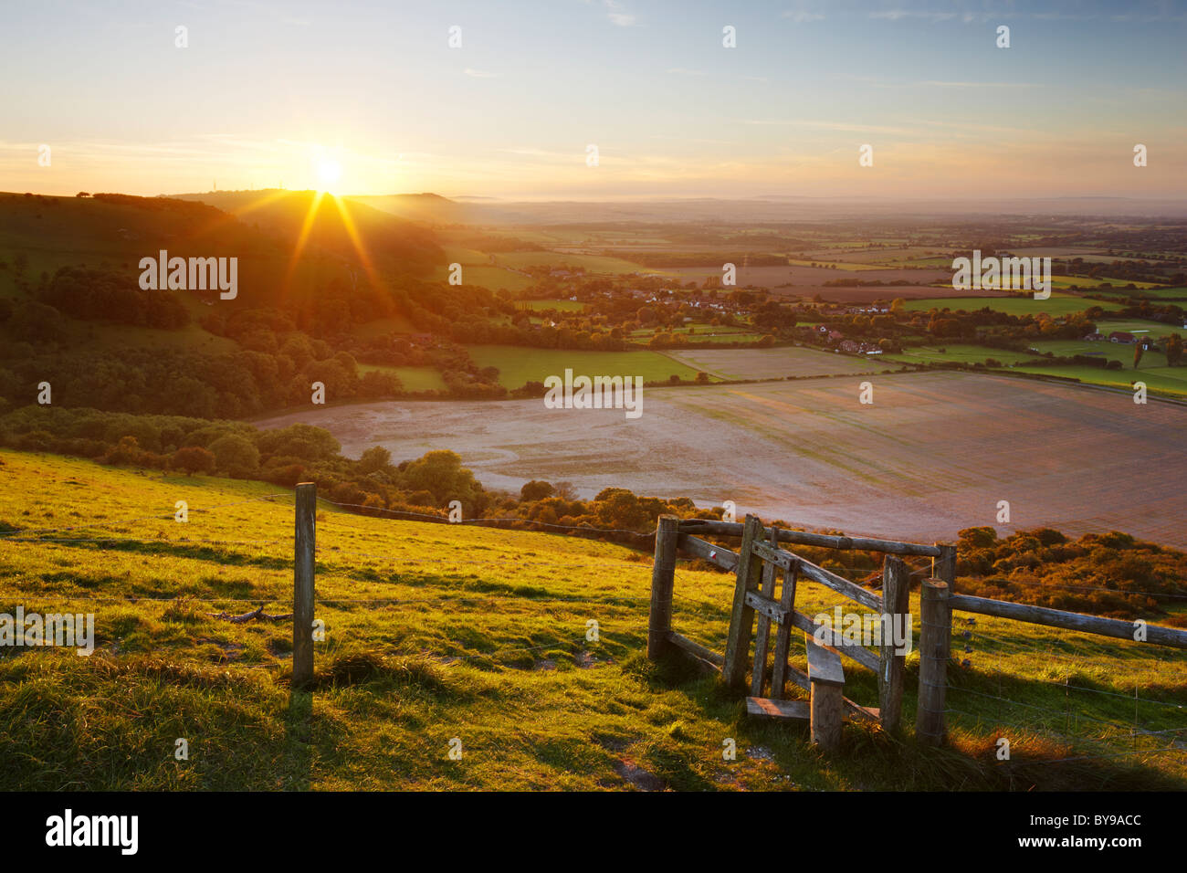 Stile with views across the West Sussex countryside. The evening sun making its descent behind the undulating Hillside. Stock Photo