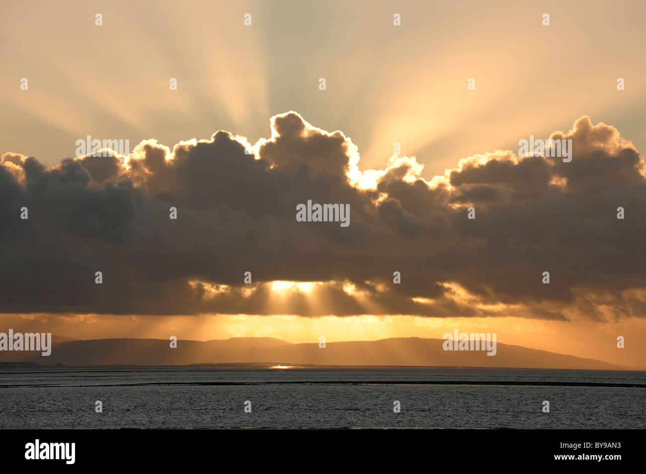 Golden sunset behind clouds - Stock Image