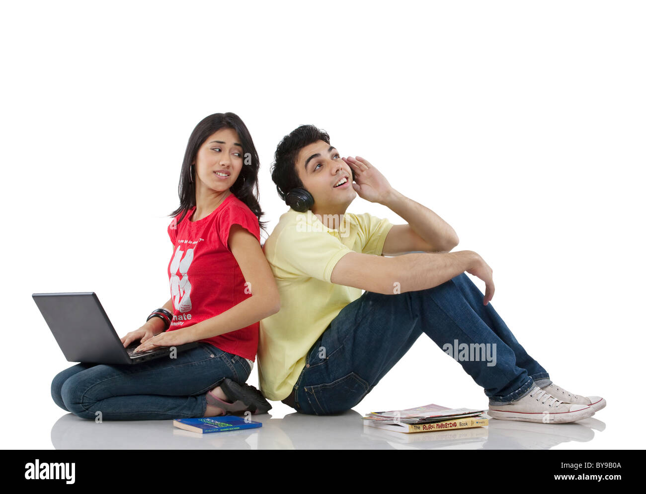 Girl sitting with a laptop while boy listens to music - Stock Image