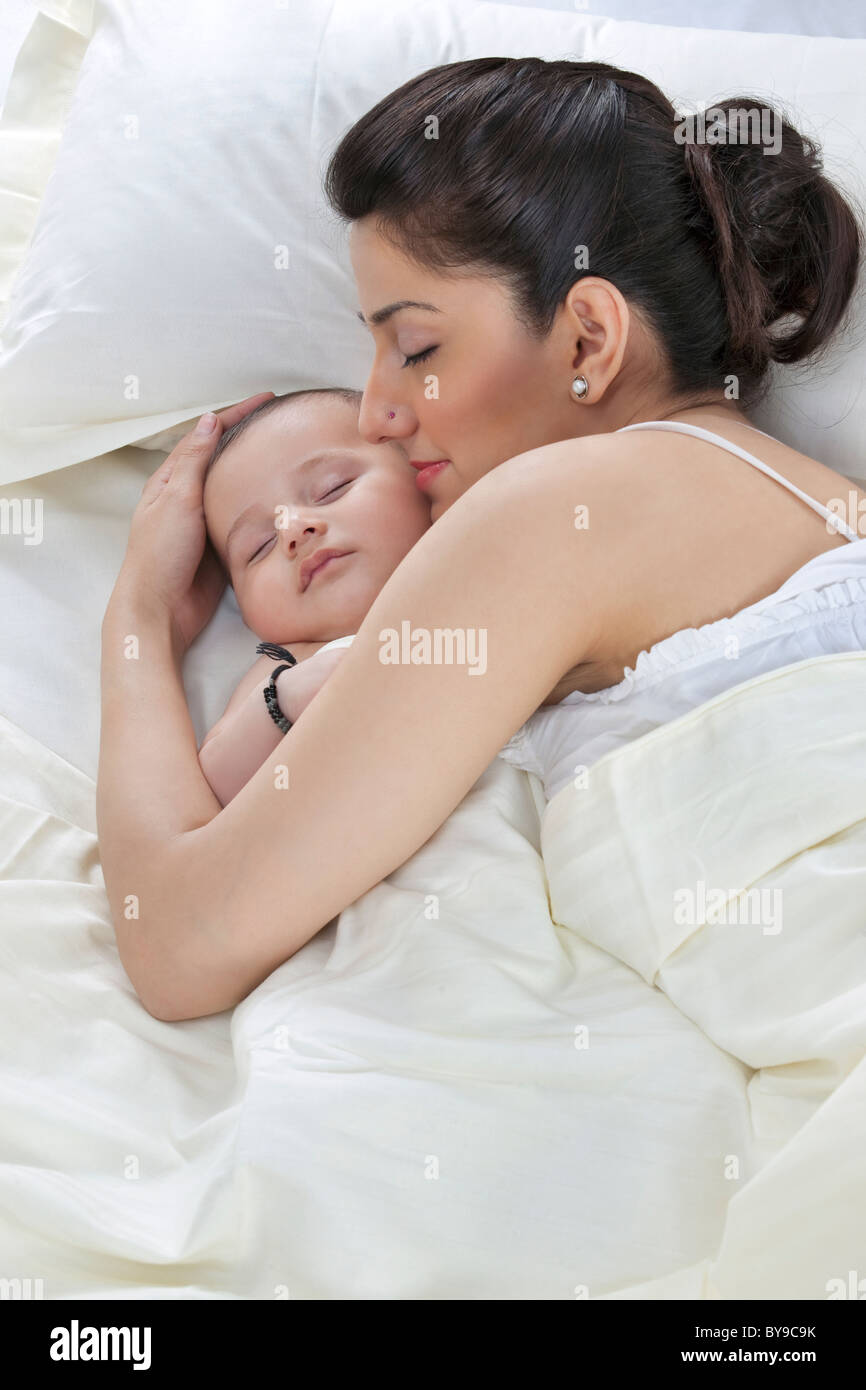 Mother sleeping with her baby - Stock Image