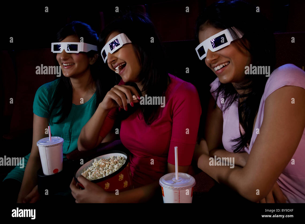 Girls watching a movie with 3-D glasses - Stock Image
