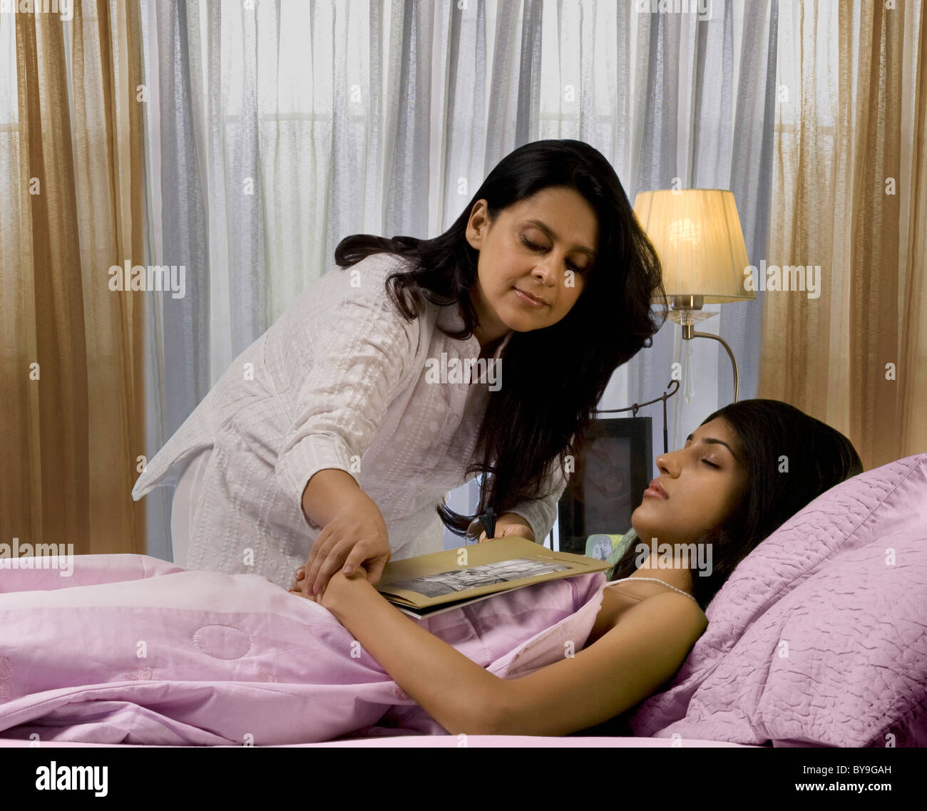 Mother removing a book from her daughters clutches - Stock Image