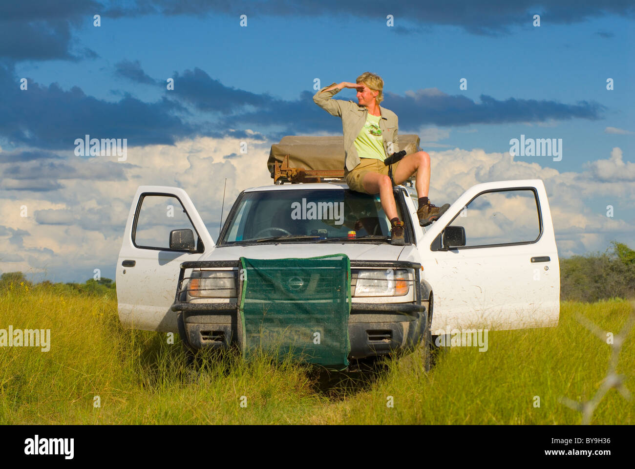 tourist sitting on four wheel drive vehicle whatching the area on a safari, Makgadikgadi National Park, Botswana, - Stock Image