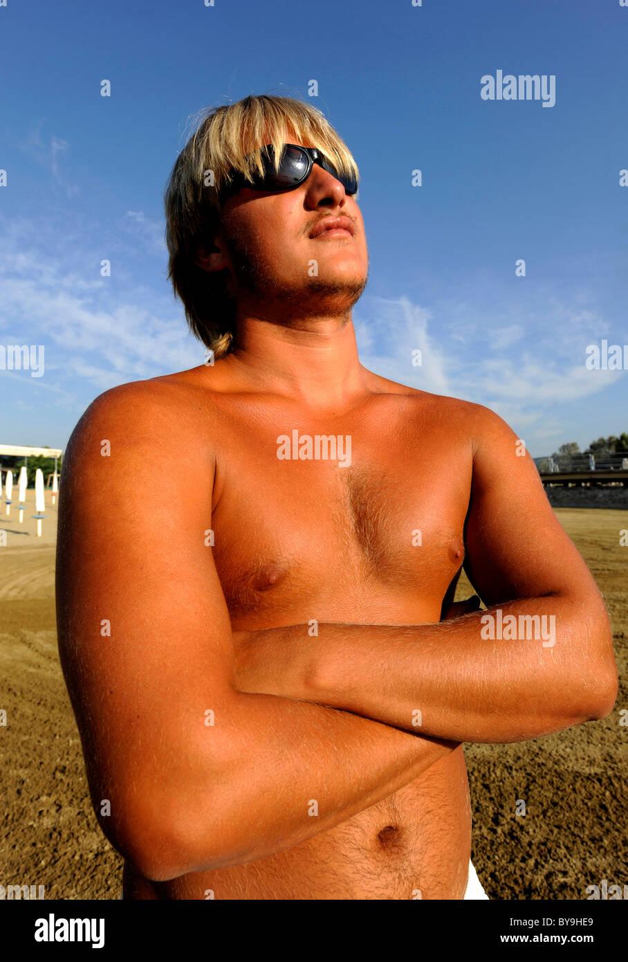 A tanned Italian lifeguard at the beach at Lake Trasimeno ,Campo del Sole, Tuoro, Umbria, Italy Stock Photo