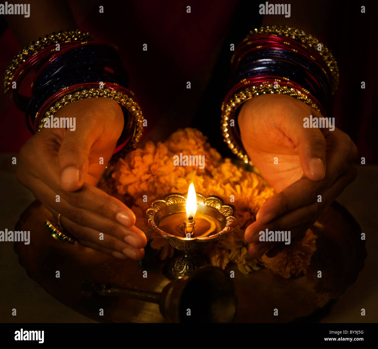 Hands cupped around a diya - Stock Image