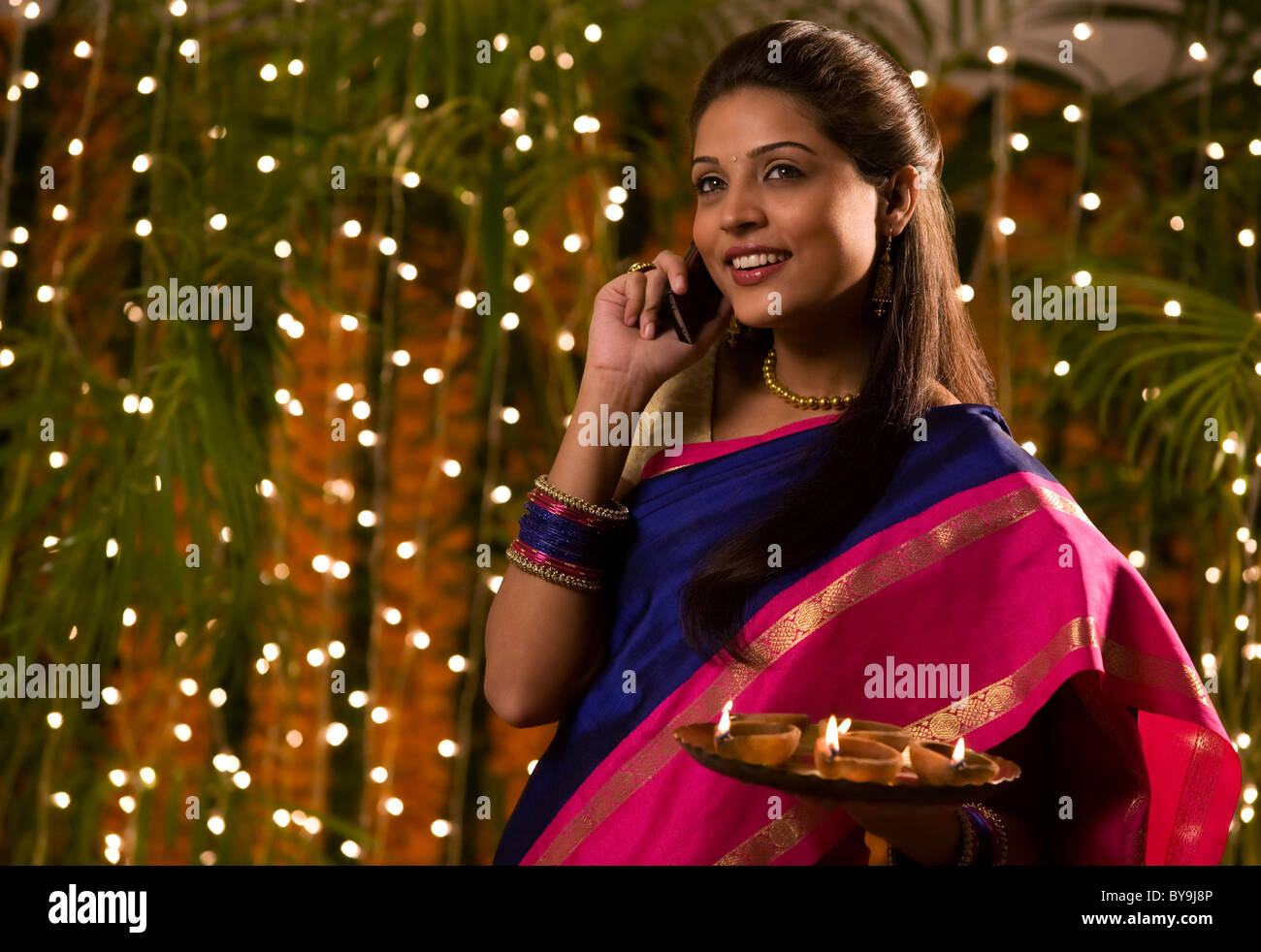 Woman talking on a mobile phone while holding a tray of diyas - Stock Image