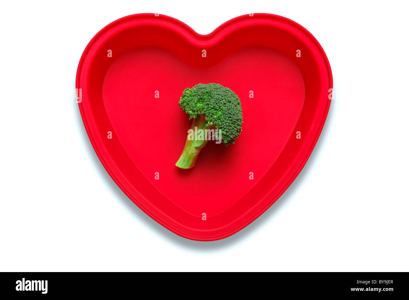 Conceptual photo of broccoli in a heart shaped dish to represent a love of the vegetable, isolated on a white background - Stock Image