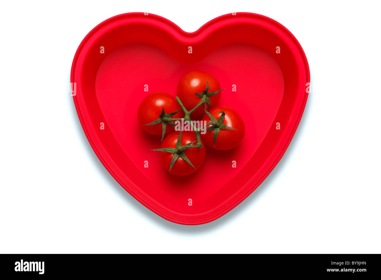 Conceptual photo of tomatoes in a heart shaped dish to represent a love of the vegetable, isolated on a white background - Stock Image