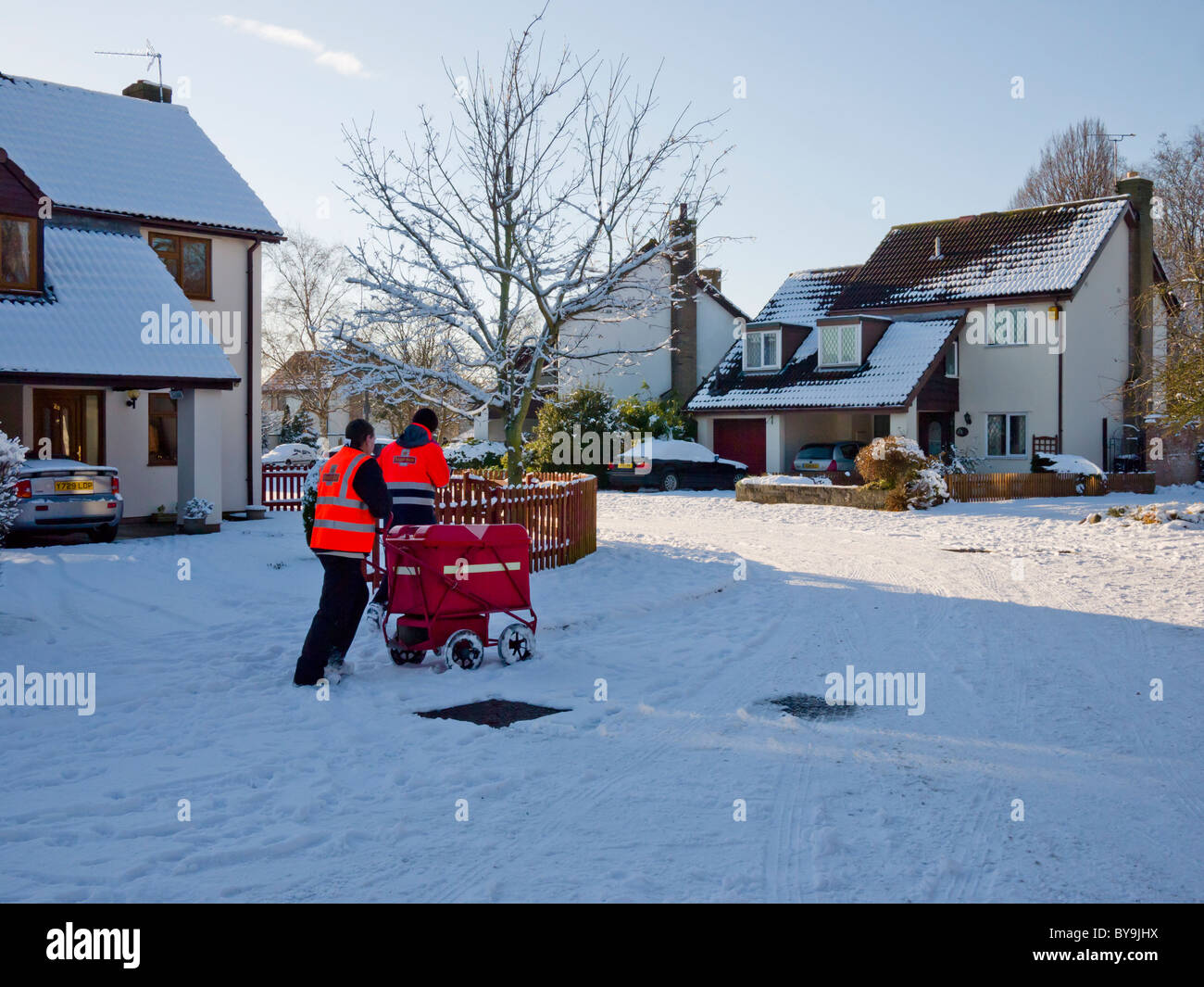 Two postmen in the street delivering mail to houses. Wrington, North Somerset, England. Stock Photo