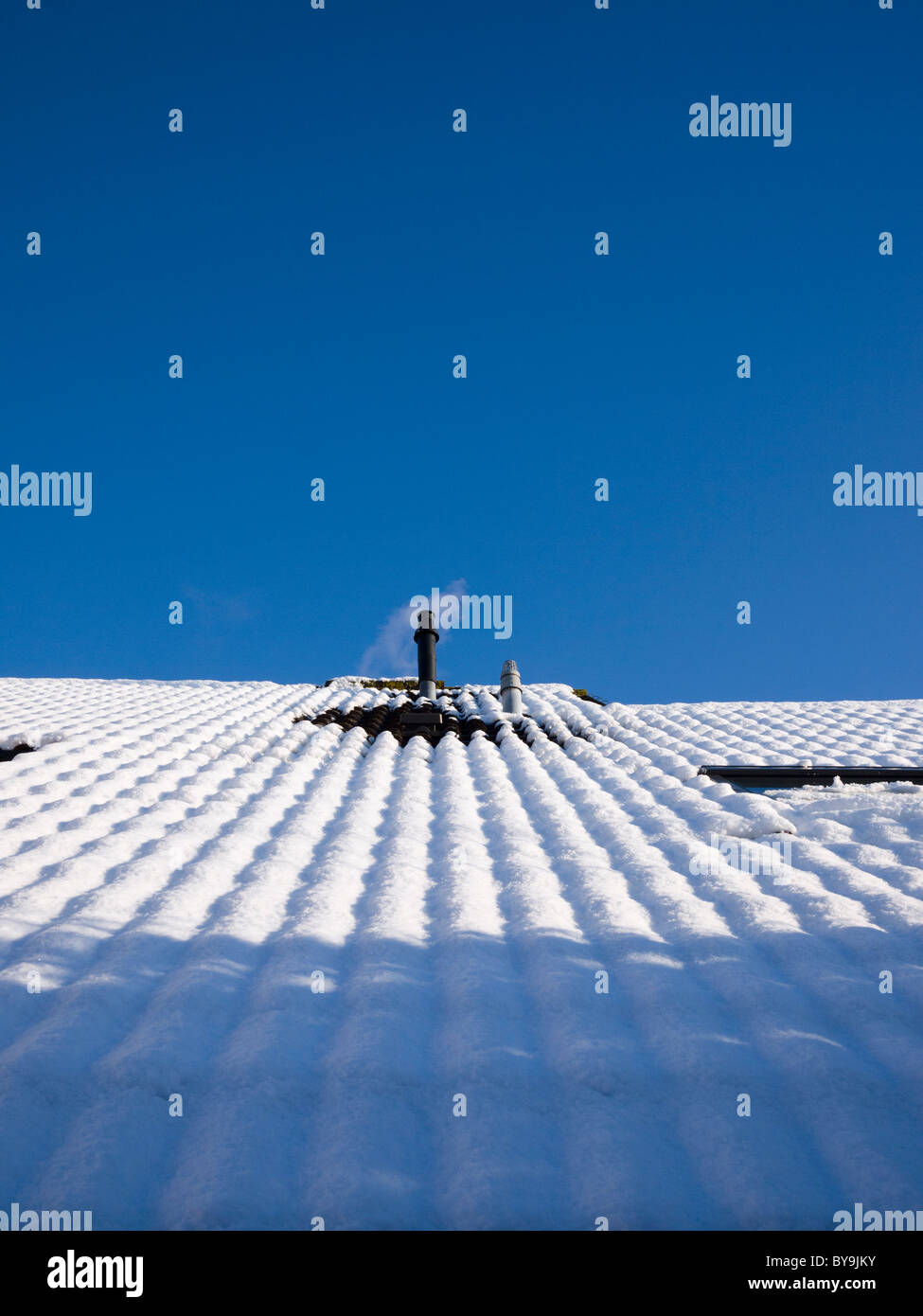 A domestic combination boiler flue on a rooftop emitting steam on a snow covered roof against a clear blue sky. - Stock Image
