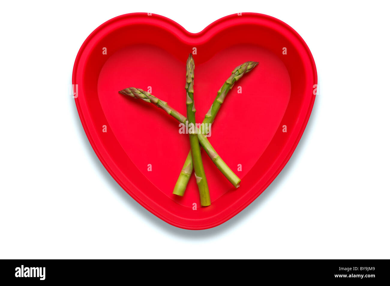 Conceptual photo of asparagus in a heart shaped dish to represent a love of the vegetable, isolated on a white background - Stock Image