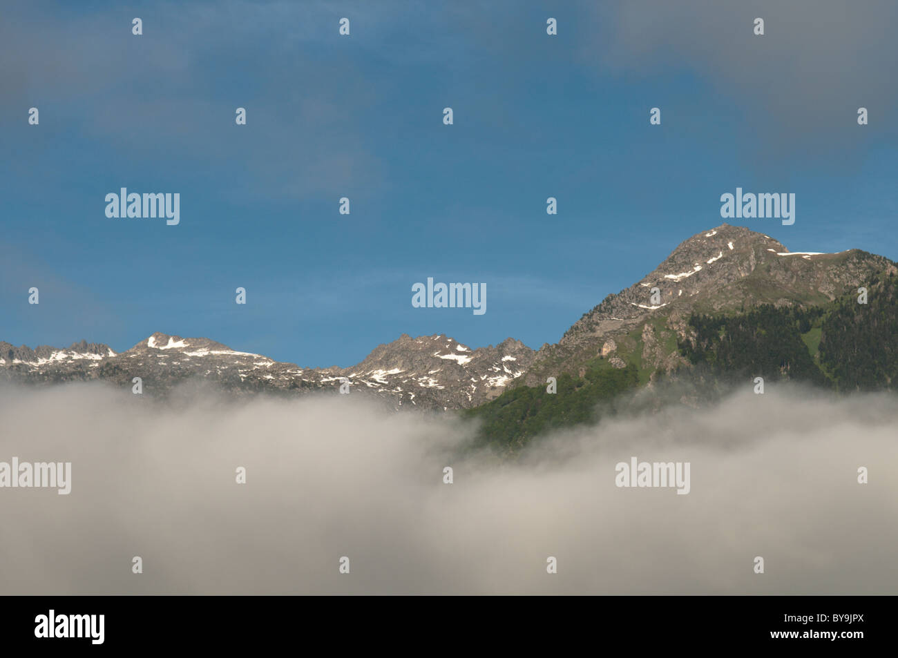 View of mountaintop seen through thinning cloud above town of Luz-Saint-Sauveur, Park National des Pyrenees, The - Stock Image