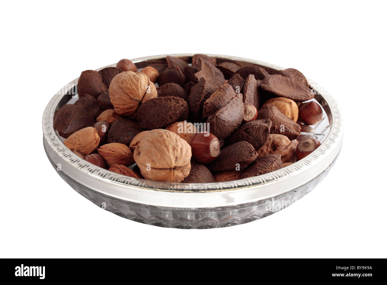 A Bowl of mixed nuts in shells on white background - Stock Image