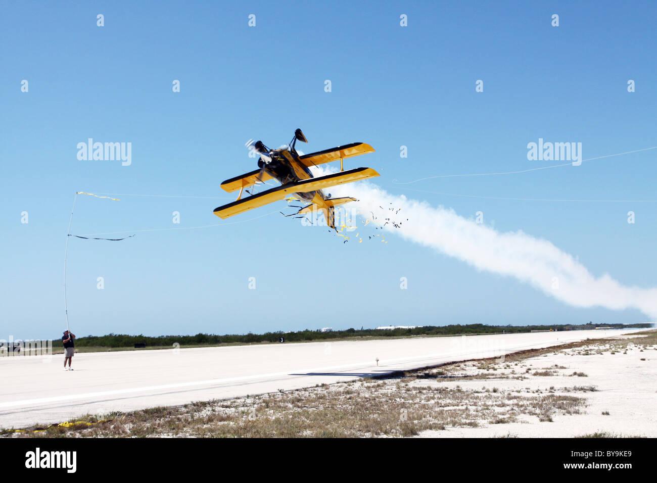 Bi=plane flying upside down. Stock Photo