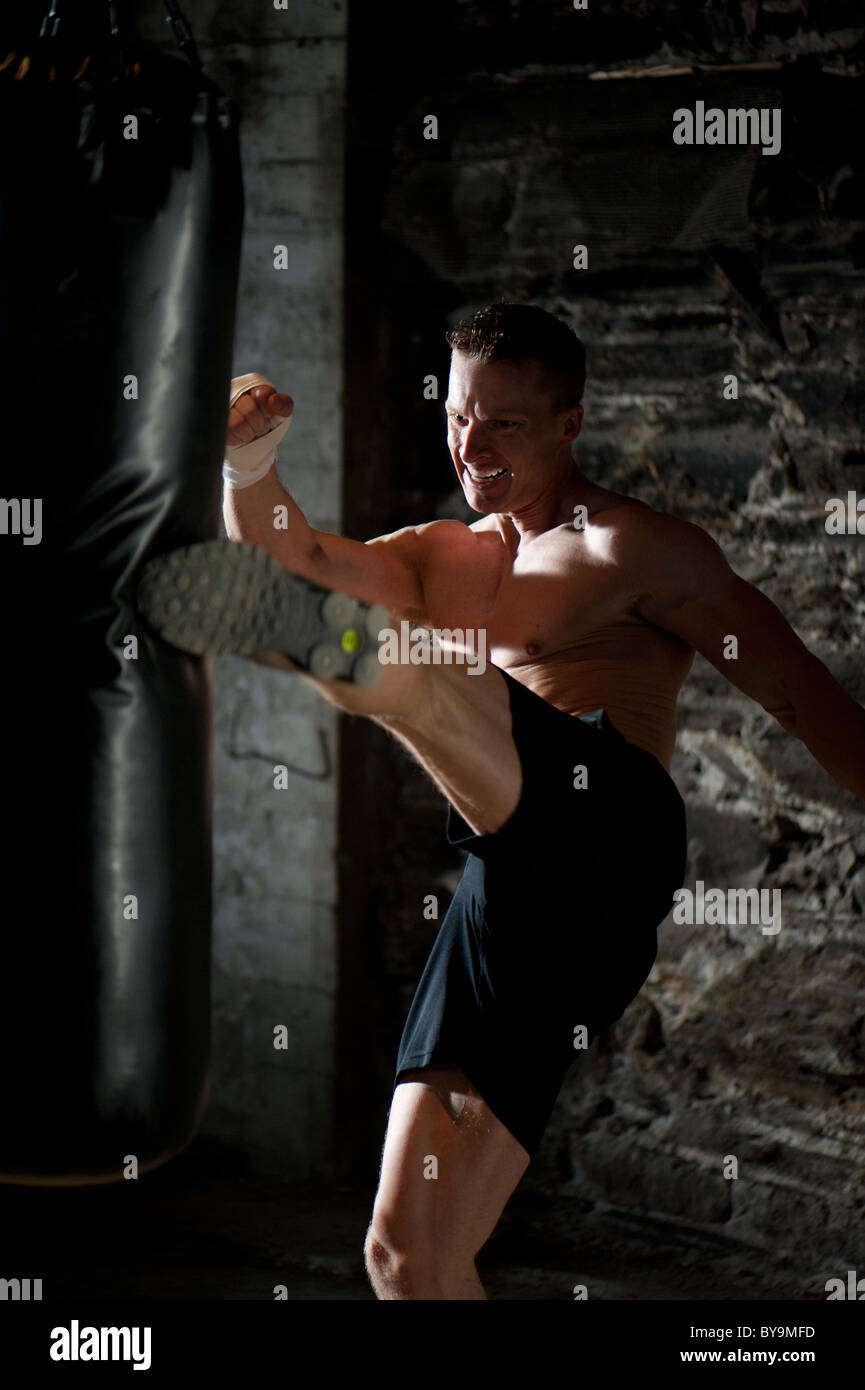 A man kick boxing at a gym. - Stock Image