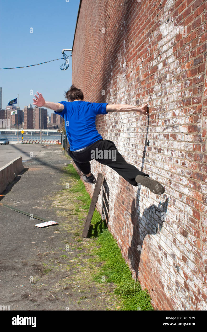 Traceur running along a wall - Stock Image