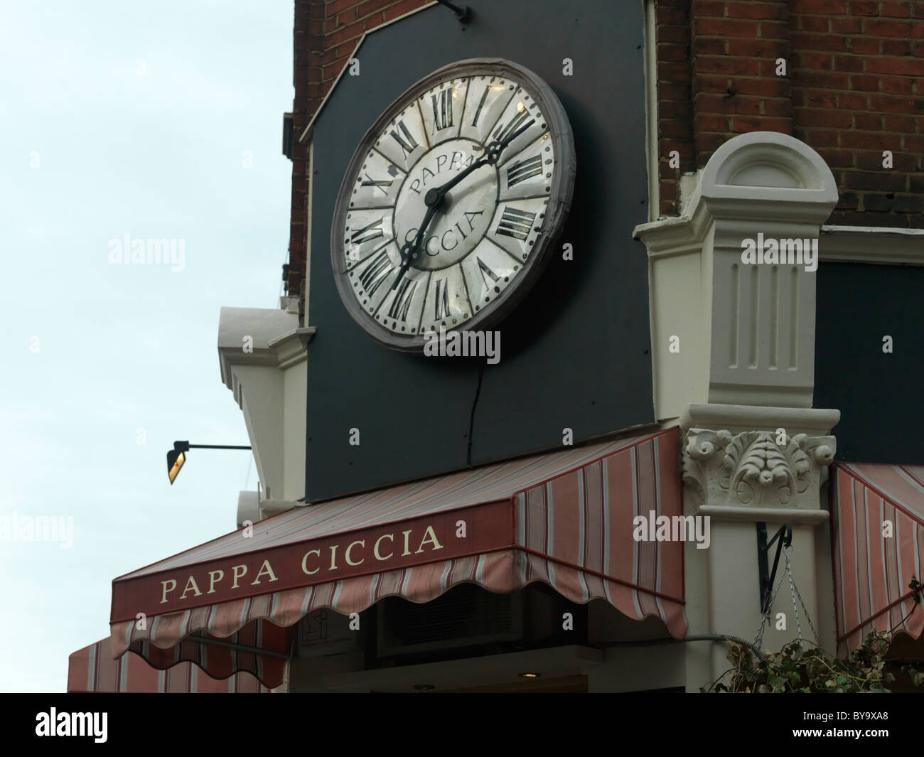 London England Large Clock With Roman Numerals Above Italian Restaurant Pappa Ciccia - Stock Image