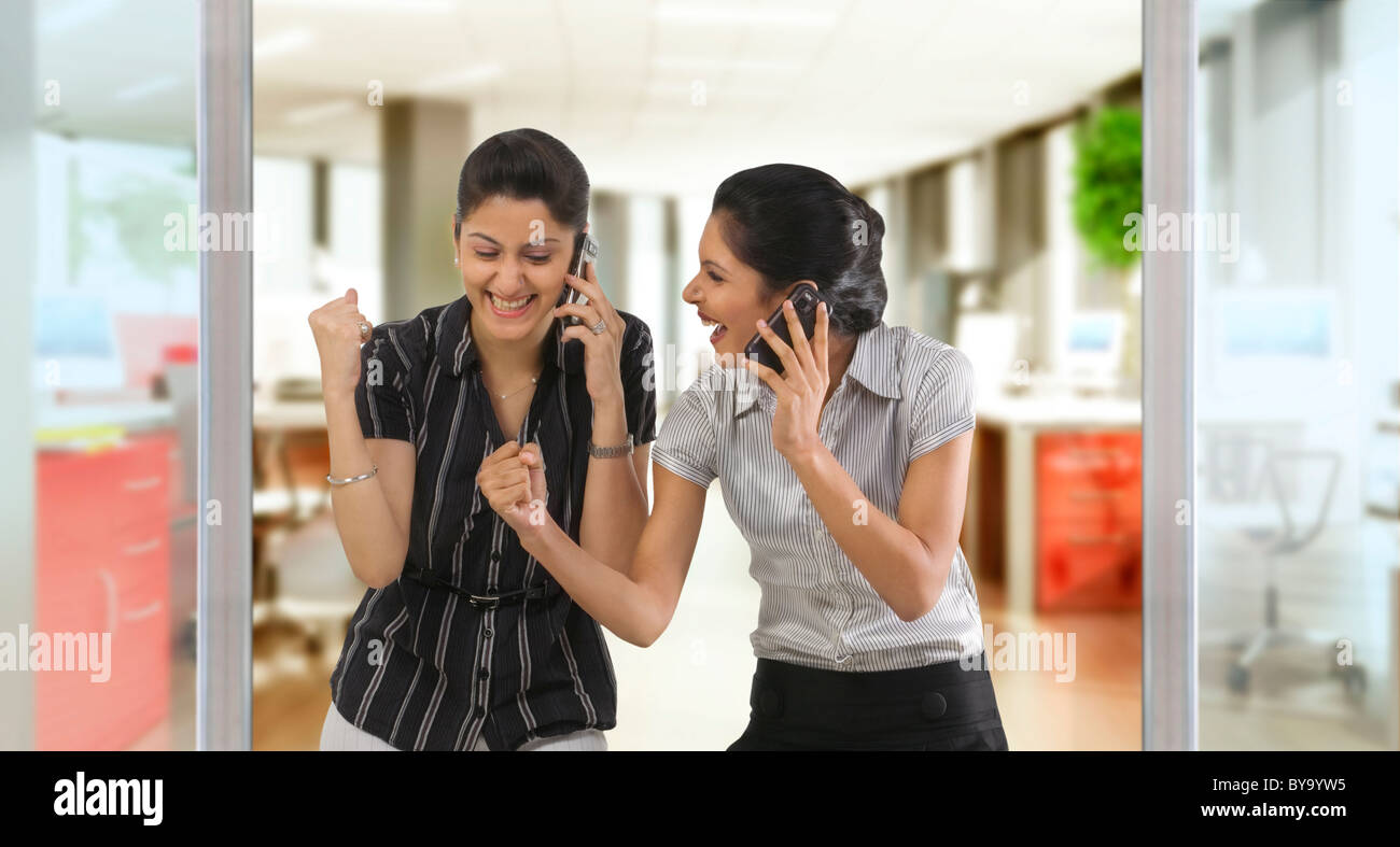 Businesswomen with mobile phones rejoicing Stock Photo
