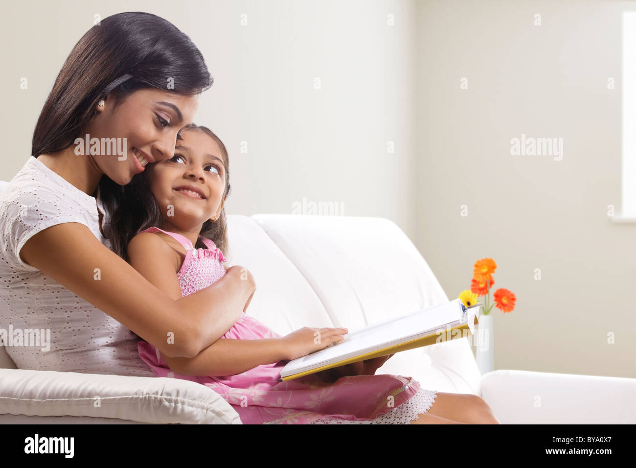 Mother and daughter with a story book - Stock Image
