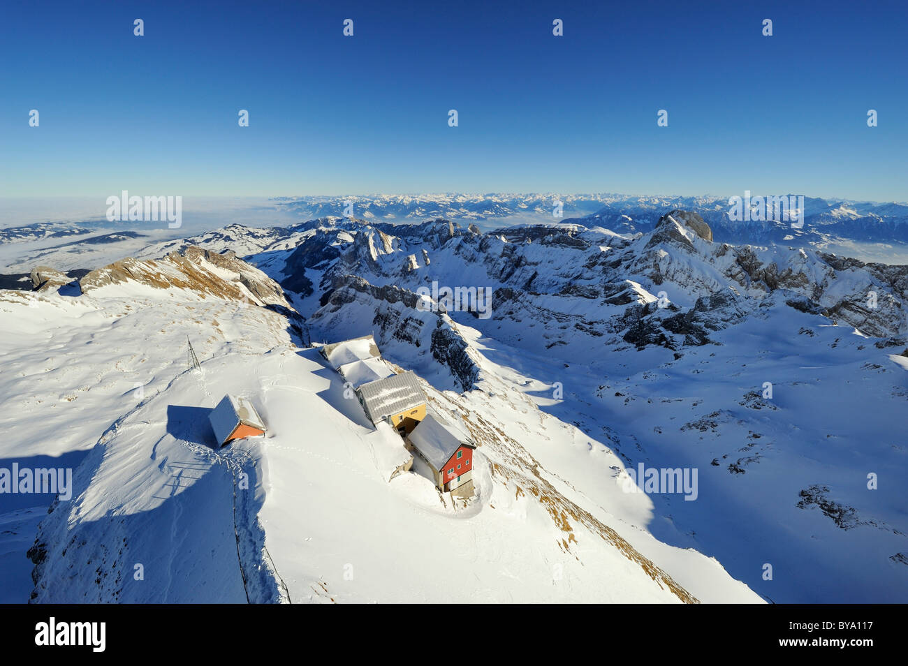 Snow-covered Alpstein massif and some mountain inns as seen from the summit of Saentis mountain, canton of Appenzell - Stock Image