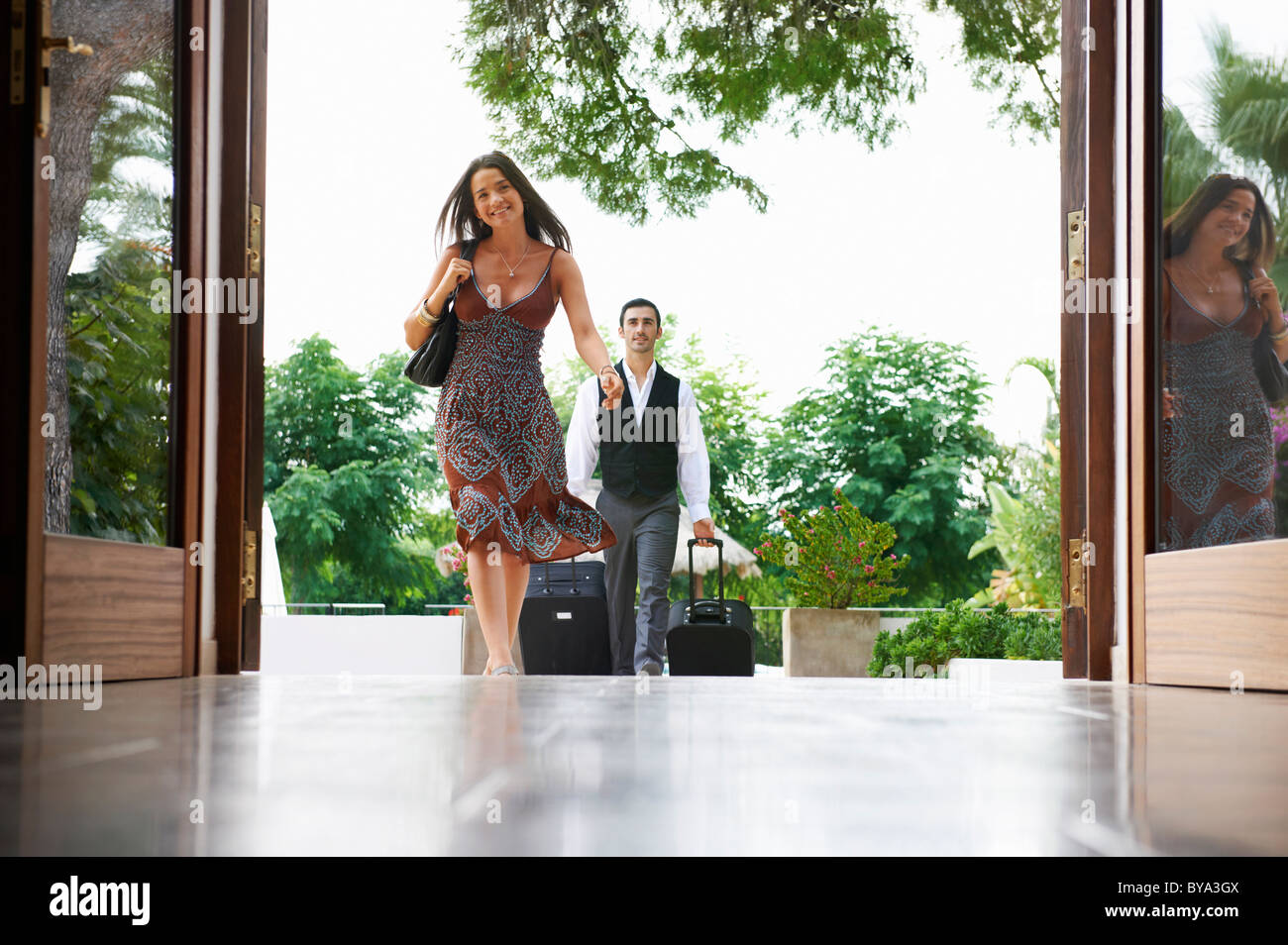 Woman entering hotel man carrying bags - Stock Image