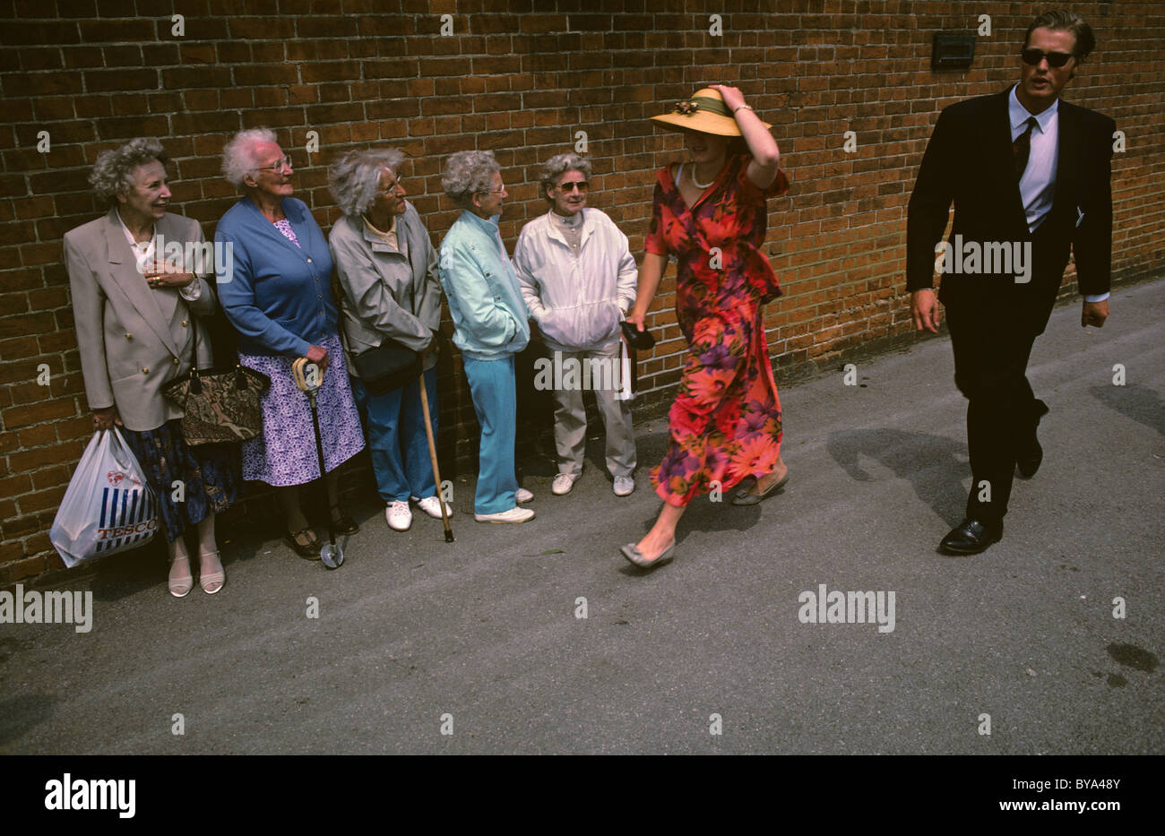 Arriving for the Royal Ascot races, young couple find themselves under scrutiny by group of elderly people-watchers - Stock Image