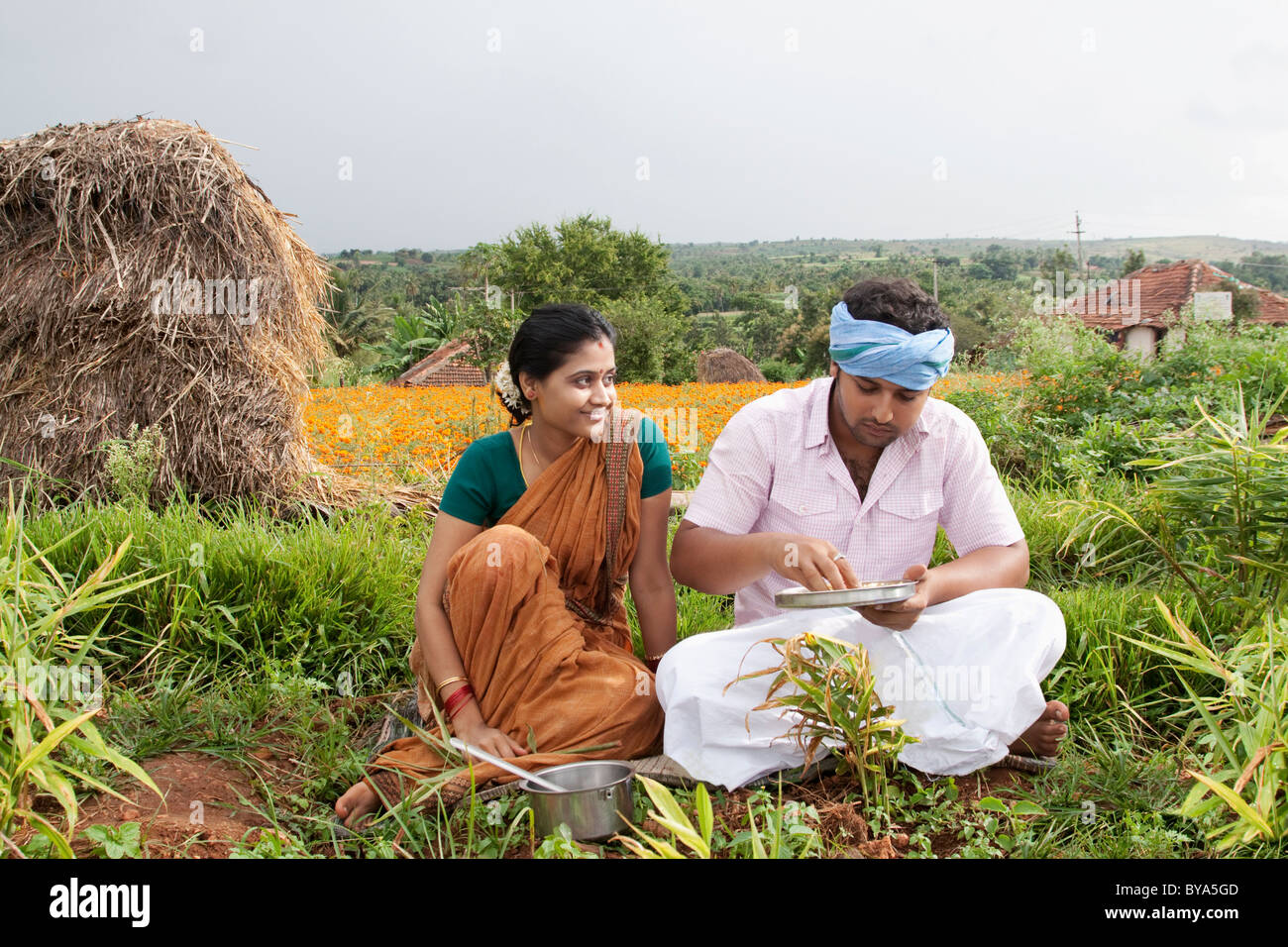 Rural man having lunch as his wife looks on - Stock Image