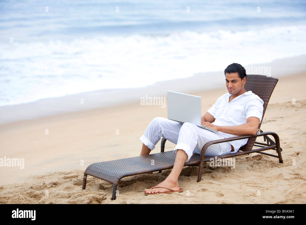 Man with a laptop at a beach Stock Photo
